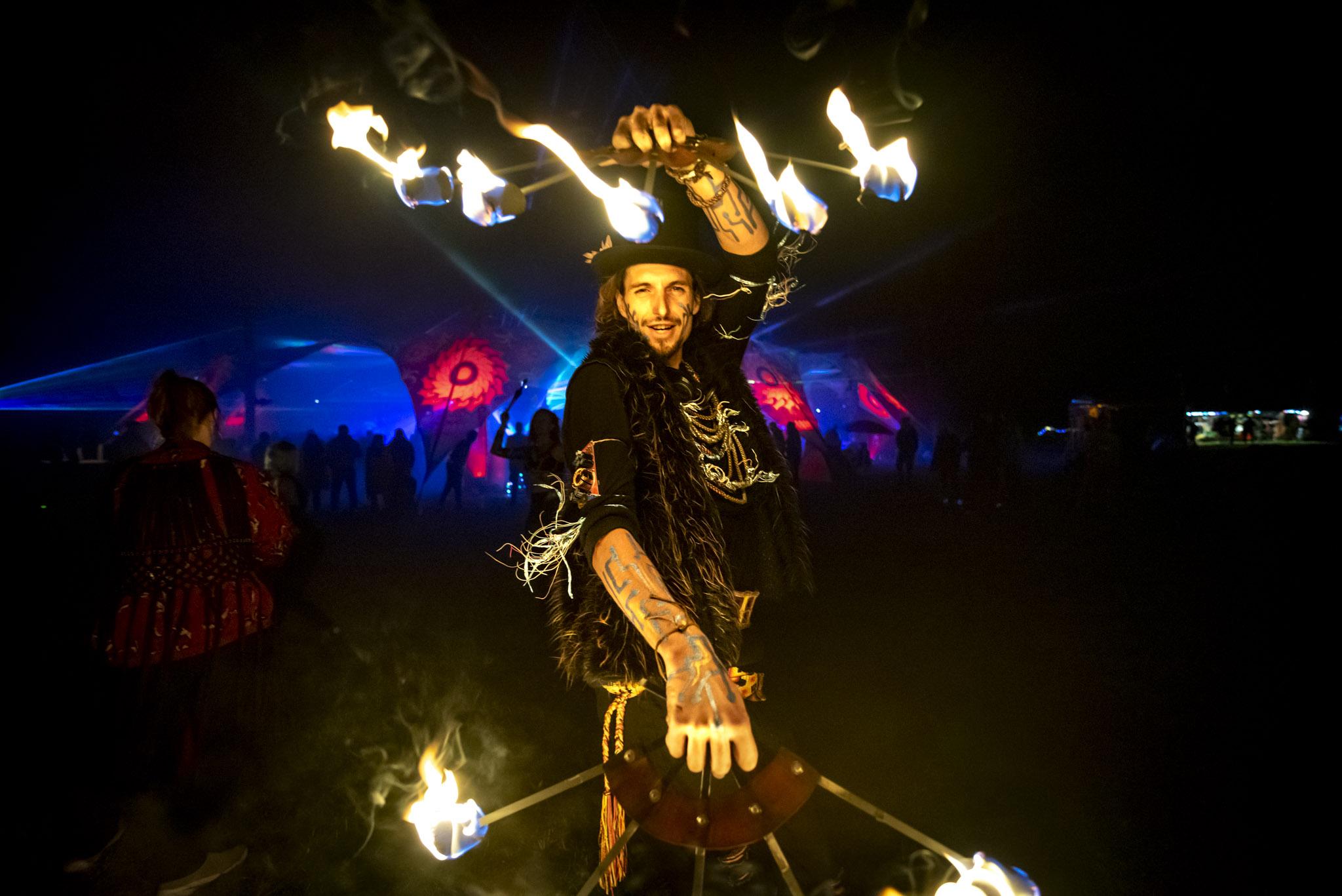 Verkleideter Feuertänzer mit Feuerfackeln in der Hand auf dem Evolution Festival
